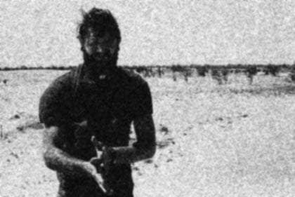 a man standing in the desert, black and white, grainy, blurred