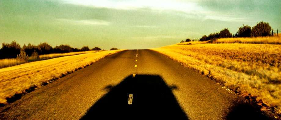 the shadow of a vehicle heading down a desert road