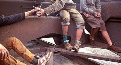 the legs of three train hoppers, young men passing a drink around and sitting on the outside of a train car as it flies down the tracks