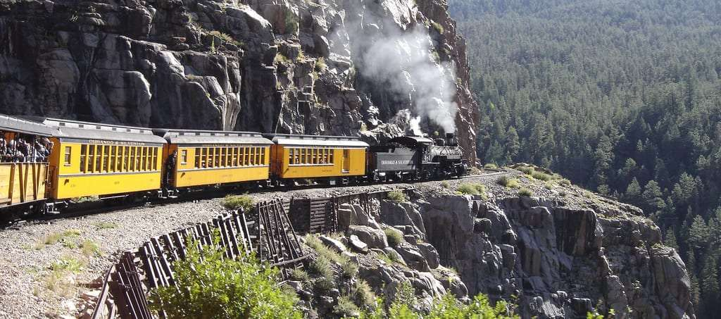 a train, smoke rising from the engine, rounds a bend high in the Rockies