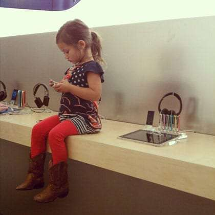 a young girl, long black pony tail, wearing red tights, boots and sitting on a shelf in an Apple store