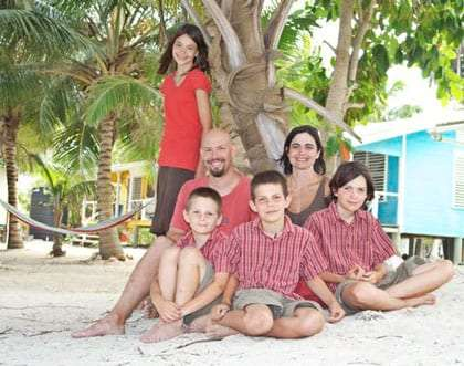 a family of six, all dressed in red and khaki, pose on a beach in some far away land