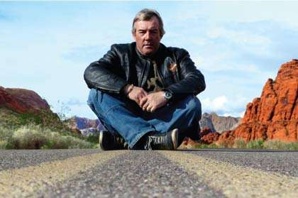 a silver haired man in leather and denim sits Indian style in the middle of faded yellow lines streaking parallel down a highway through some southwestern US desert
