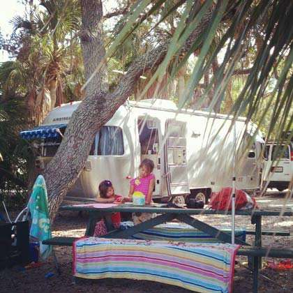 two young girls at a picnic table, surrounded by palm trees and an Airstream travel trailer