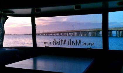 a purple sunset through an Airstream's bay windows