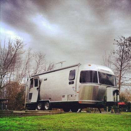 a silver travel trailer, an Airstream, parked on a grassy knoll, a brooding cloudy sky looming