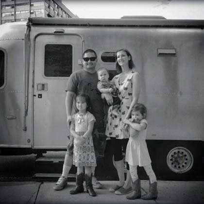 a family of five poses in front of an Airstream