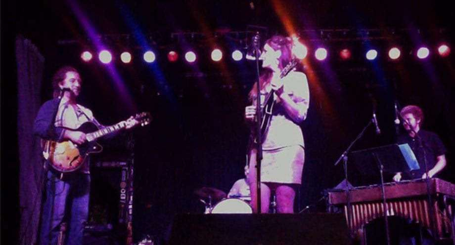 purple lights dim a stage full of gypsies, a woman on mandolin lovingly stares at the guitarist as a wild haired drummer fills the background