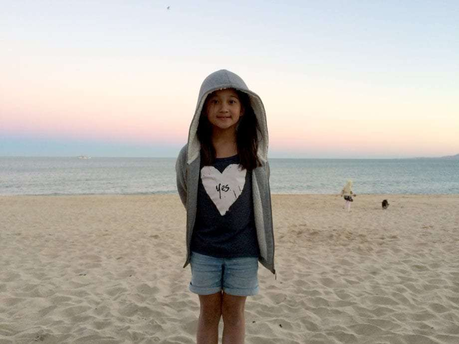 a young girl wearing a shirt that says yes stands on the beach