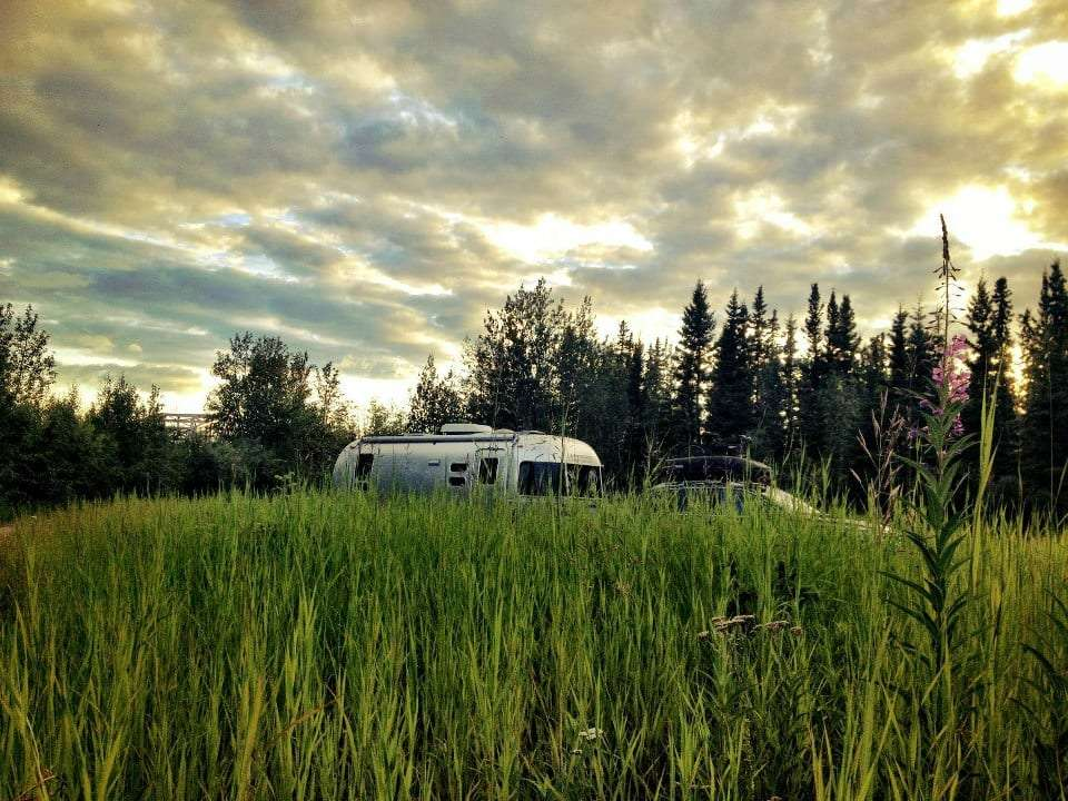 a silver Airstream peeks just over a field of grass