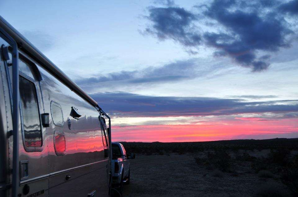pink divides the silhouette of earth off into the horizon while the evening sky turn blue, all of it reflecting in the side of an aluminum travel trailer