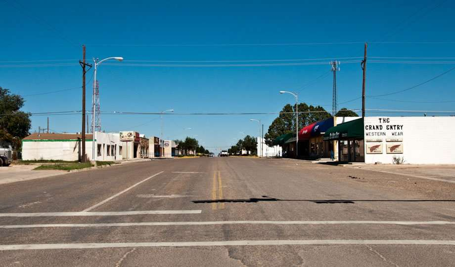 an empty street in a small town, a sign painted on the side of a white brick store reads The Grand Entry Western Wear