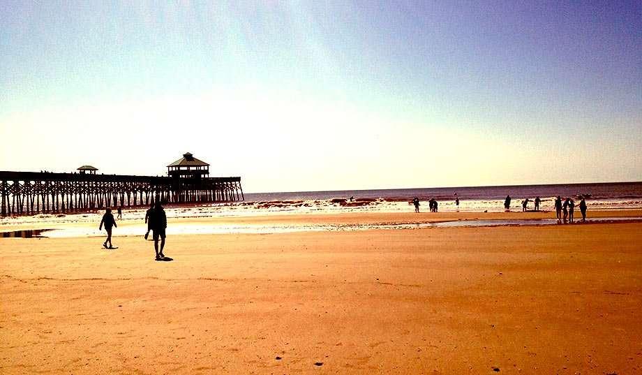 a pier juts into the atlantic, blue sky contrasting orange beach sand