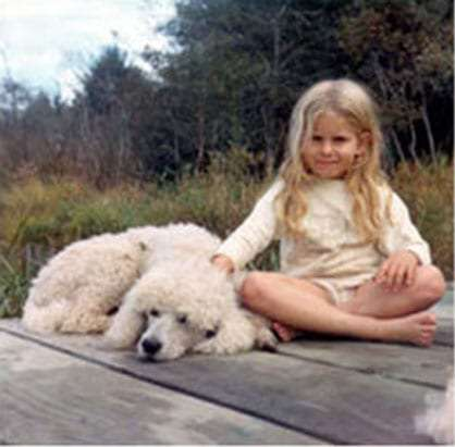a young girl with blond hair stairs peculiarly into the shot, her hand on a large white poodle