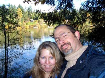 the Airstreaming couple takes a self-portrait against a reflecting forest lake