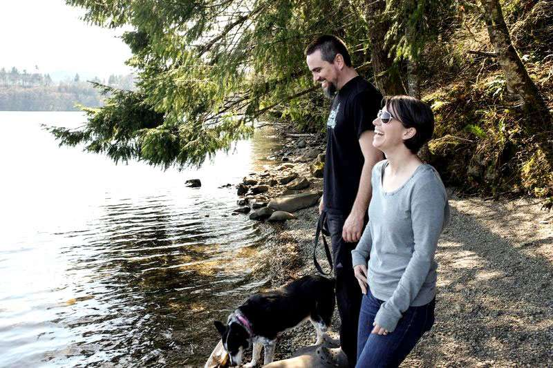 lakeside, a couple laughs, the man holding the leash to a dog, the woman her stomach