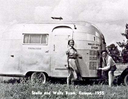 a black and white photo of Wally Byam and his wife Stella standing in front of their small Airstream in 1955