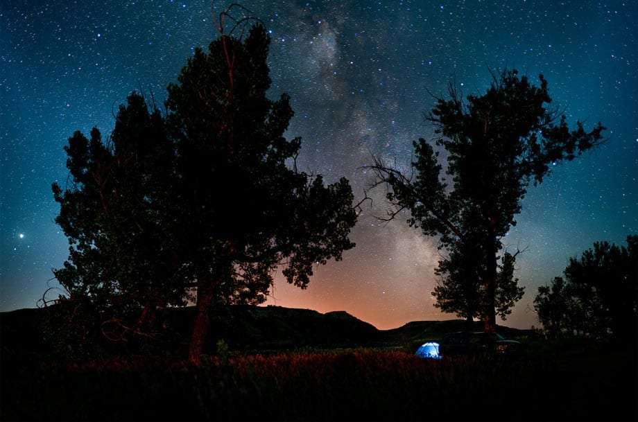 a tent is illuminated from the inside, billions of stars shine through the night sky silhouetting the treeline above
