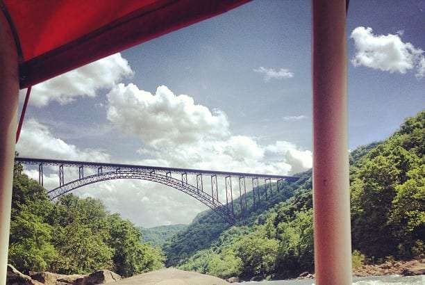a massive bridge spans over a river, a forested gorge, from the point of view of a speedboat
