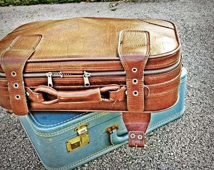 two vintage suitcases, stacked atop one another