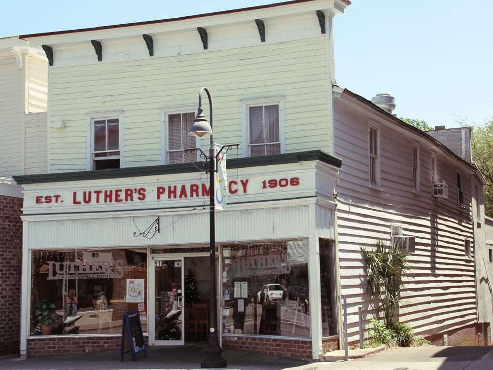 an old white building with red letters reading Luthers Pharmacy