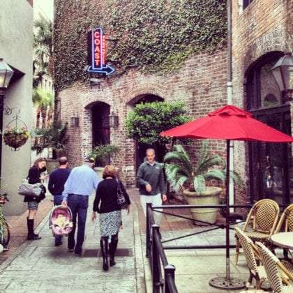 an alley full of people and restaurants, ivy lined, in Charleston, SC