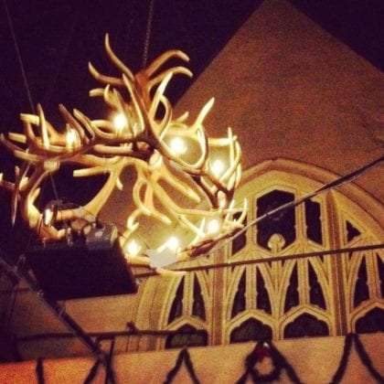 a chandelier made of antlers hangs in a church