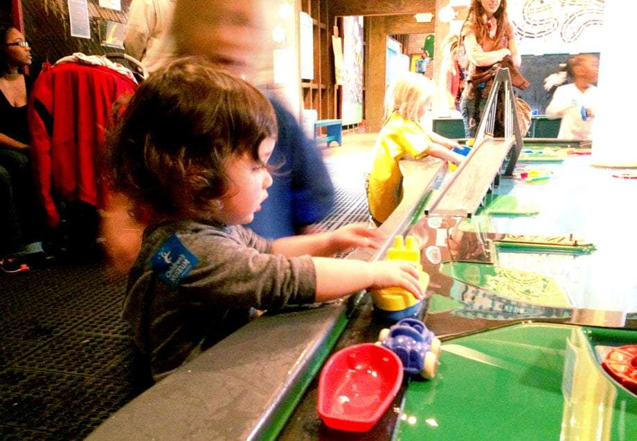 a boy plays with toy boats in a museum