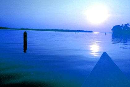 a canoe rides into a blue sunset