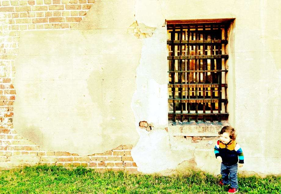 a young boy runs from the barred windows of an old jail