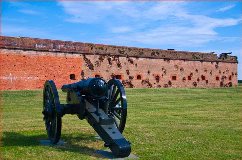 a cannon sits in a field of green, damaged walls of Fort Pulaski in the background