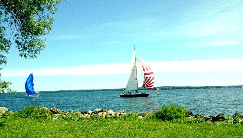 two sailboats ride the top of Lake Superior in Wisconsin, the leader sporting red and white sail