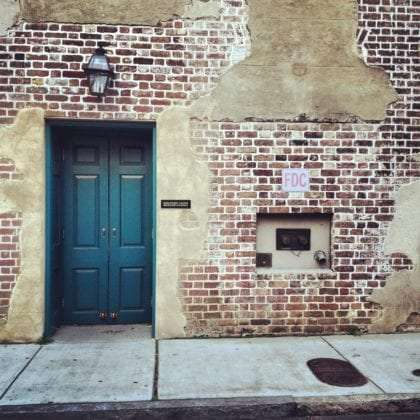 a patched up brick wall, a blue door
