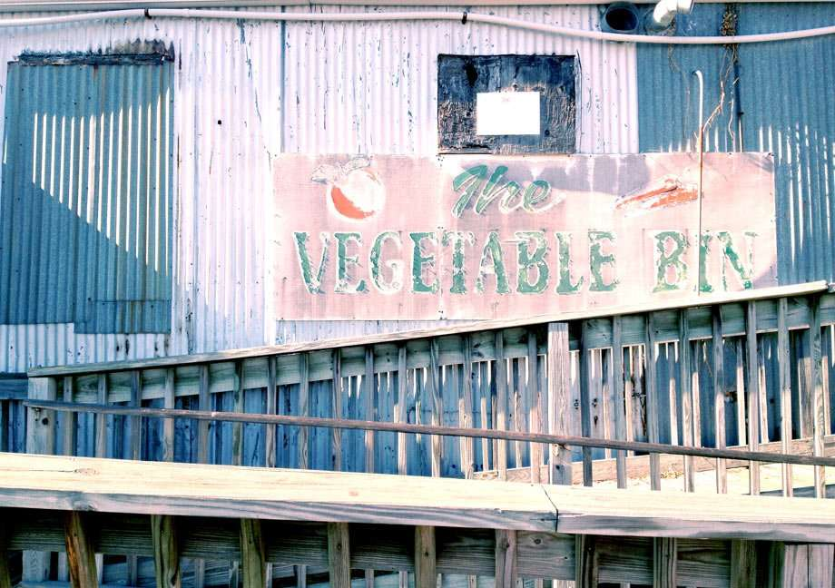an old sign reads vegetables