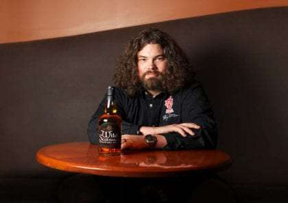 Jeff Topping, long haired owner of Wild Scotsman Whisky, sitting at a table with his product