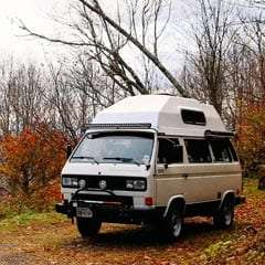 a high-top Vanagon in the autumn foliage