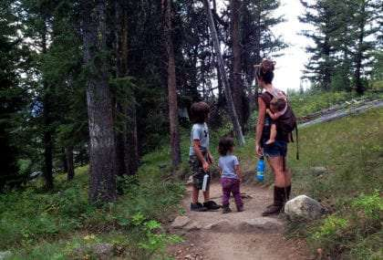 a beautiful young woman hikes with her two children, the third, an infant, strapped to her back