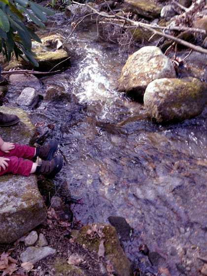 a pair of little feet, in little boots, dangle over a creek in the Smoky Mountains