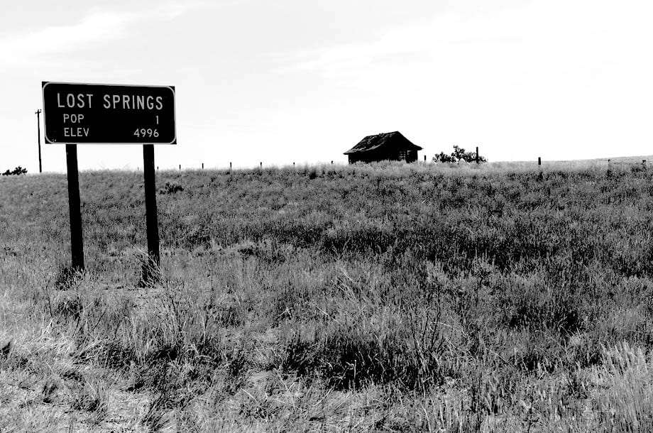 a sign reads Population 1, Elevation 4996, Lost Springs, a lone barn sits in the background