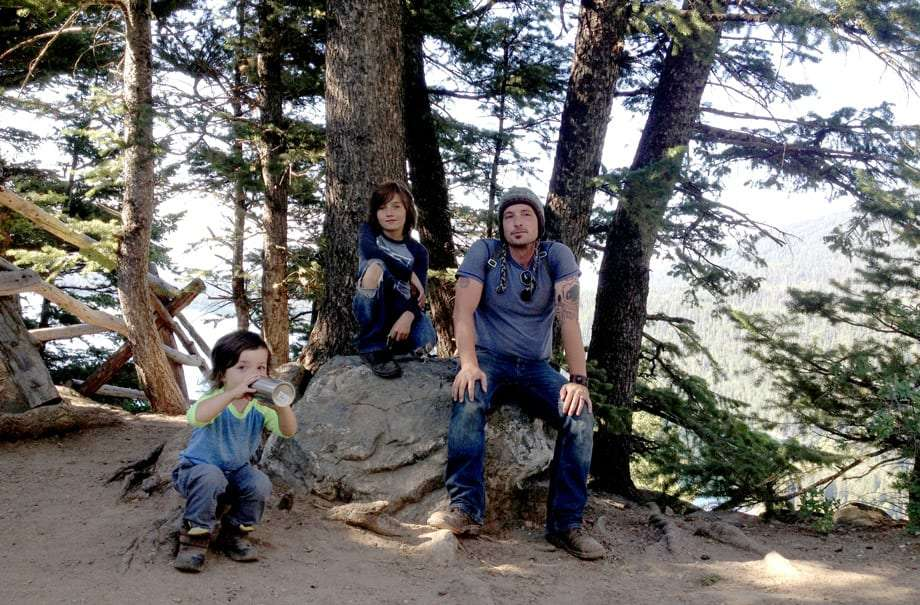 a dad and two of his boys rest at the top of a mountain