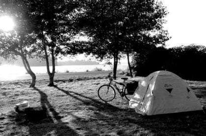 a bicycle, a tent, and a yet to be made fire sit near a large body of water in Newport, Oregon