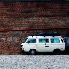 a VW Vanagon Westfalia parked in front of a brick wall in asheville, NC