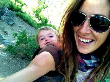 a baby rides in a carrier on his mama's back while she hikes
