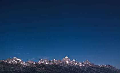 the tops of the Grand Tetons, a dark blue sky rises above