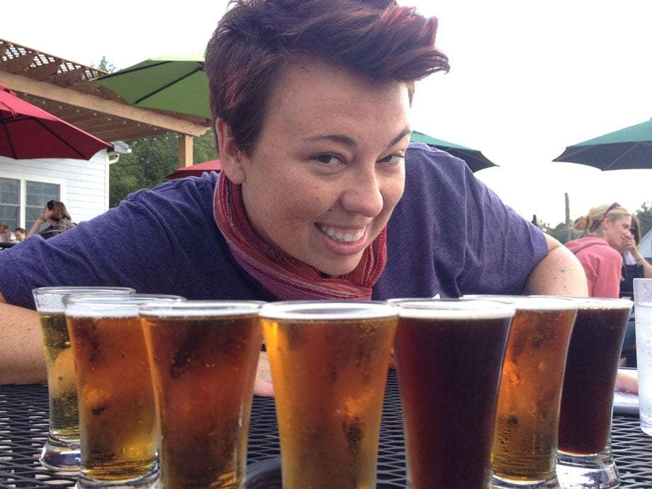 a young woman smiles, a host of beers in pints lined afront her