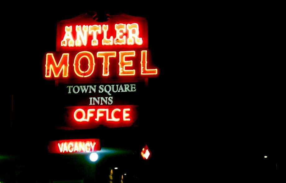 a neon sign reads Antler Motel, Town Square Inns, Office, Vacancy