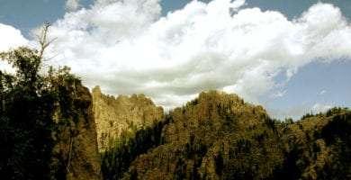 rocky cliffs and dark black forest