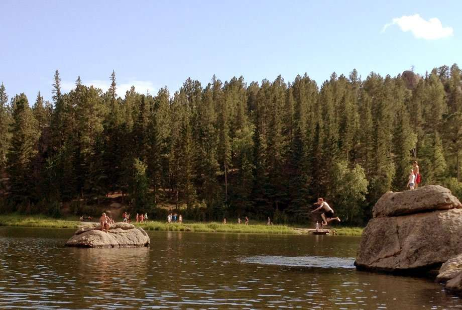 kids jumping off of high rocks into a lake