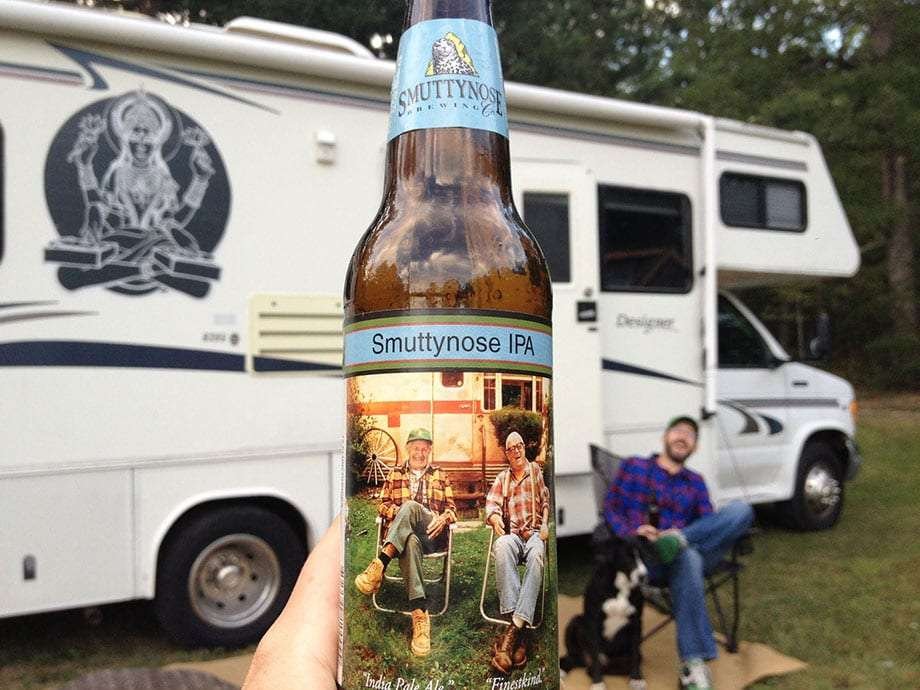 a bottle of Smuttynose IPA held up, an RV, a drinker and a dog in the blurred background