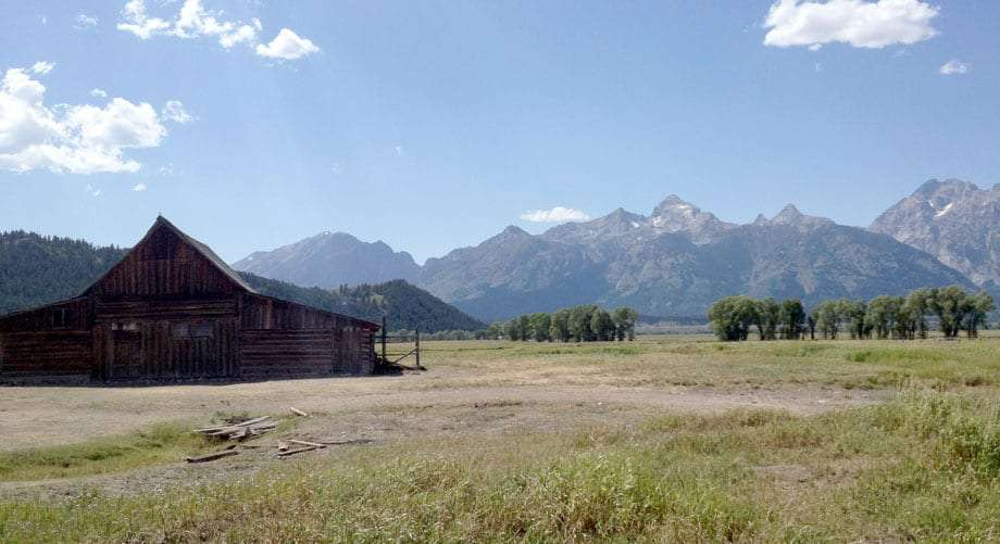 a barn, the roof of which echoing the Teton mountains in the background